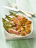 Green asparagus,raw ham and rye bread cheese-topped dish