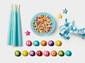 'Happy Birthday' written on Smarties and a blue paper cup full of sugar balls for decorating cakes, ribbon and blue birthday candles