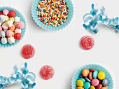 Blue paper cups full of sugar balls for decorating cakes