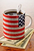 Cup of coffee in a mug with the American flag on it and dollar bills