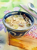 Almond milk soup with porridge, grapes, cinnamon and coconut