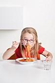 Kleines Mädchen isst Spaghetti alla Bolognese