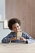 Junge isst eine Tafel weisse Schokolade