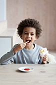 Boy eating a cone of french fries and ketchup