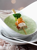 Cream of broccoli soup with a sausage and salmon mini brochette