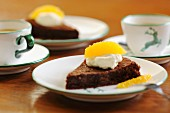 Slice of chocolate cake with cream and fresh orange
