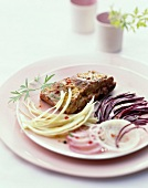 Spare ribs coated in strong mustard, thinly sliced red and white cabbage