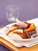Sliced chicken breast coated in breadcrumbs with roast vegetables