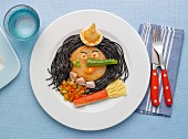 Squid ink noodles,vegetables calamaries and surimi on a plate in the shape of witch's face