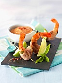 Shrimps wrapped in bacon and basil with cocktail sauce