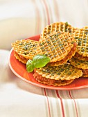 Basil and olive oil waffle cookie sandwiches filled with sun-dried tomato cream