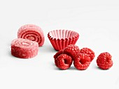 Raspberry rolled candies and paper cups