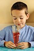 Junge trinkt Erdbeersirup mit Strohhalm