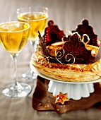 Galette des rois with a chocolate crown, glasses of cider