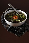 Black rice, green cabbage and smoked trout soup with walnut pistou