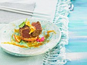 Tuna coated in sesame seeds with orange and green apple salad