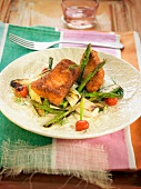Pieces of breaded salmon with green asparagus, pak-choi cabbage and cherry tomatoes