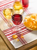 Glasses of red wine with crisps on a table