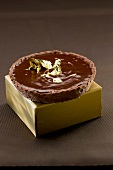 All chocolate tartlet with golden flakes
