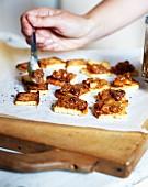 Hände verteilen mit einem Löffel Foie Gras auf Toastbrot