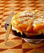 Mango tatin tart sprinlkled with grated coconut