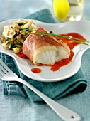 Cod wrapped in raw ham with creamed red pepper sauce