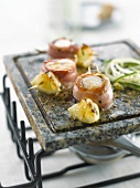 Scallops wrapped in bacon and sliced zucchinis on a cooking stone