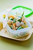 Reissalat mit Jakobsmuscheln im Plastikbehälter zum Mitnehmen
