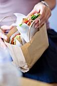 Frau packt Sandwich fürs Büro in eine braune Papiertüte