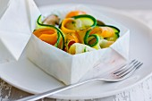 Thin strips of vegetables cooked in a square pack of wax paper
