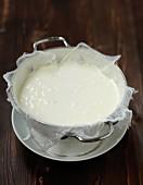 Draining the homemade lemon yoghurts through a mousseline cloth