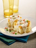 Star-shaped flaky pastry hearts garnished with vegetables and mushrooms in bechamel sauce