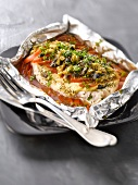 Chicken with mustard, tomatoes and green and black olives cooked in aluminium foil