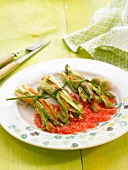 Small bundles of sliced asparagus and carrots with tomato sauce