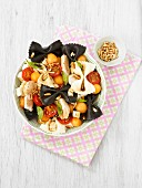 Black and white pasta salad with chicken, cherry tomatoes and melon balls