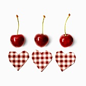 Composition with cherries and checkered hearts