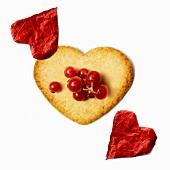 Herzförmiges Plätzchen mit roten Johannisbeeren und roten Papierherzen