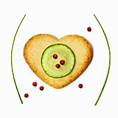 Heart-shaped biscuit ,sliced zucchini and pink peppercorns