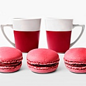 Raspberry macaroons and two cups