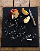 Apfel auf einer Tafel mit dem Spruch 'An apple a day keeps the doctor away'
