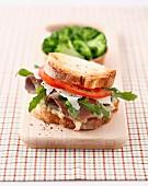 Lamb,parmesan,rocket lettuce and tomato sandwich