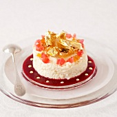 White chocolate mousse decorated with candied fruit and gold flakes,summer fruit puree
