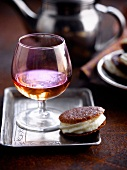 White chocolate mousse sandwich biscuit and a glass of Calvados