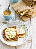 Sliced brown bread with peanut butter,sliced apples and bananas