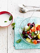 Fresh fruit salad with white sauce and mint