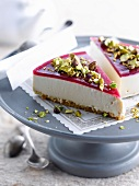 Cheesecake topped with raspberry jelly and crushed pistachios