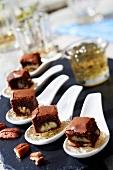 Pekannuss-Schoko-Brownie auf Vanille-Rum-Gelee mit Algenflocken auf Probierlöffeln