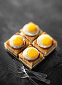 Ham and cheese mini taosted sandwiches topped with fried quail's eggs