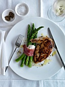 Grilled chicken breast,bundle of green asparagus tied with raw ham and goat's cheese