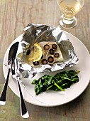 Cod, lemon and olives cooked in aluminium foil